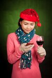 Asian girl with christmas hat ,wine and mobile phone Royalty Free Stock Image
