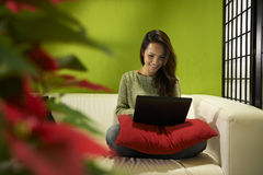 Asian girl with computer sitting on sofa at home Royalty Free Stock Photo