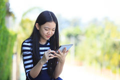 Asian girl and computer tablet in hand standing with toothy smil Royalty Free Stock Image