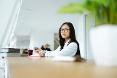 Asian girl in coworking using textbooks and wireless connection to network Royalty Free Stock Photography