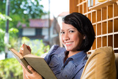Asian girl with cup reading book Stock Photo