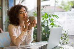 Asian girl with a cup of tea and a laptop Royalty Free Stock Photography