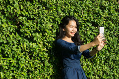 Asian girl cute smile face with mobile phone on green park royalty free stock image