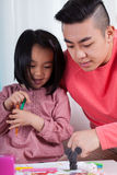 Asian girl and dad drawing together Stock Images