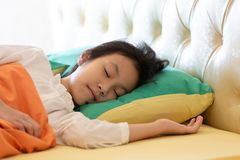 Asian girl deep sleeping on her bed with little smiling dream,good health and relaxation royalty free stock image