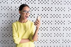 Asian girl is demonstrating her bad emotions. How is it possible. Angry young woman is standing against white wall and holding modern mobile phone. She is Stock Photo