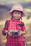 Asian girl with digital camera in beautiful outdoor. Vintage pic Royalty Free Stock Photos
