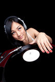Asian Girl DJ. An Asian girl DJing on red turntable isolated on black Royalty Free Stock Photos