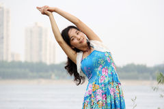 Asian girl do yoga. In front of a river: bend her waist Royalty Free Stock Photo