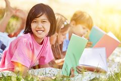 Asian girl is doing homework in the garden. Together with her friends Stock Photo