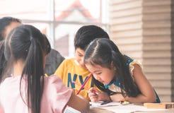 Asian girl drawing in kindergarten art classroom. Asian girl is drawing in kindergarten art classroom royalty free stock photo