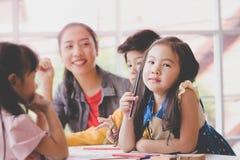 Asian girl drawing in kindergarten art classroom. Asian girl is drawing in kindergarten art classroom stock photo