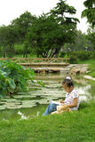 Asian girl drawing by river. Chinese girl drawing with teddy bear on picturesque, riverbank Stock Photo