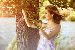 Asian girl in dress near a tree. Holds the branches of the Royalty Free Stock Photos