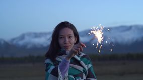 An Asian girl dressed in a blanket holds a sparkler in her hands. Sunset, snowy mountains in the background stock video