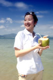 Asian girl drinking coconut on the beach Royalty Free Stock Images