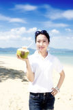 Asian girl drinking coconut on the beach Stock Images