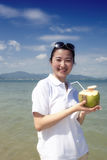 Asian girl drinking coconut on the beach Stock Image
