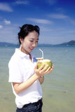 Asian girl drinking coconut on the beach Stock Photos