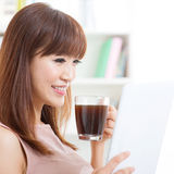 Asian girl drinking coffee while using tablet Stock Photos
