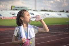 Asian girl drinking water from plastic bottles after jogging, little girl drink thirsty water due to hot weather after run in the royalty free stock image