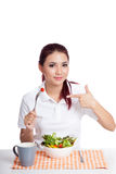 Asian girl eat salad with pointing hand sign Royalty Free Stock Photos