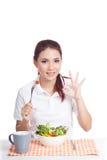 Asian girl eat salad show ok hand sign Royalty Free Stock Photography
