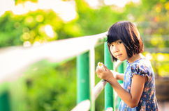 Asian girl eating bun in park, warming light. Royalty Free Stock Photo