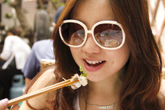Asian girl eating with chopsticks. Asian girl with long hair and big sun glasses eating with chopsticks at an asian local open air eatery stock photos