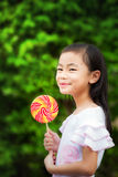 Asian girl eating a colorful candy. With green nature background Stock Photo