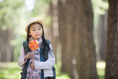 Asian girl eating a colorful candy. With green nature background Stock Photography