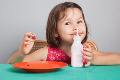 Asian girl eating a donut with milk. The asian girl eating a donut with milk stock photo