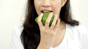 Asian girl eating fruit, avocado. Clean food for health and weig Royalty Free Stock Image