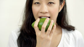 Asian girl eating fruit, avocado. Clean food for health and weig Stock Photo