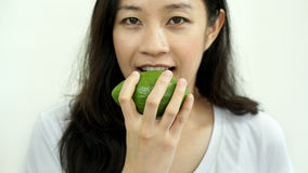 Asian girl eating fruit, avocado. Clean food, healthy and weight Stock Photo