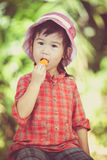 Asian girl eating ice cream in the summer on blurred nature back Stock Photo