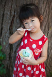 Asian girl eating ice cream in the summer day. Outdoors. Stock Photo