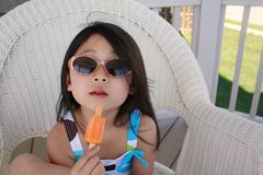 Asian girl eating ice pop with sun glasses stock photos