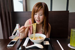 Asian Girl Eating Japanese Ramen. A cute Thai girl is eating a Japanese Ramen in the resturant. This is urban life Royalty Free Stock Photography