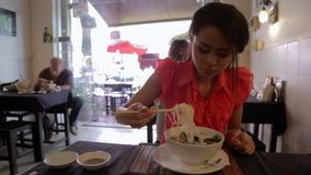 Asian girl eating noodle in a local restaurant, phnom penh Stock Photography