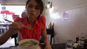 Asian girl eating noodle in a local restaurant, phnom penh Royalty Free Stock Images