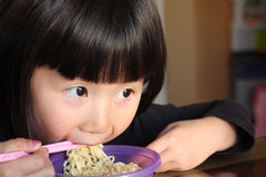 Asian girl eating noodles Stock Photos