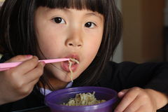 Asian Girl Eating Noodles Stock Images