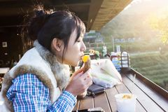 Asian girl eating sweet potato in warm sunlight royalty free stock photo