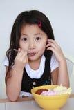 Asian girl eatingbowl of ice cream royalty free stock image