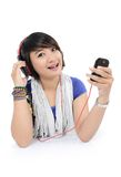 Asian girl enjoys listening to songs. From his cell phone, on white background Royalty Free Stock Photo