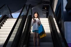 Asian girl on an escalator stock photo