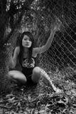 Asian girl escaping. Through an open fence stock photography