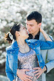 Asian girl and european guy kissing against of blossoming almond Royalty Free Stock Photo
