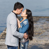 Asian girl and european guy kissing on concrete pier Royalty Free Stock Photography